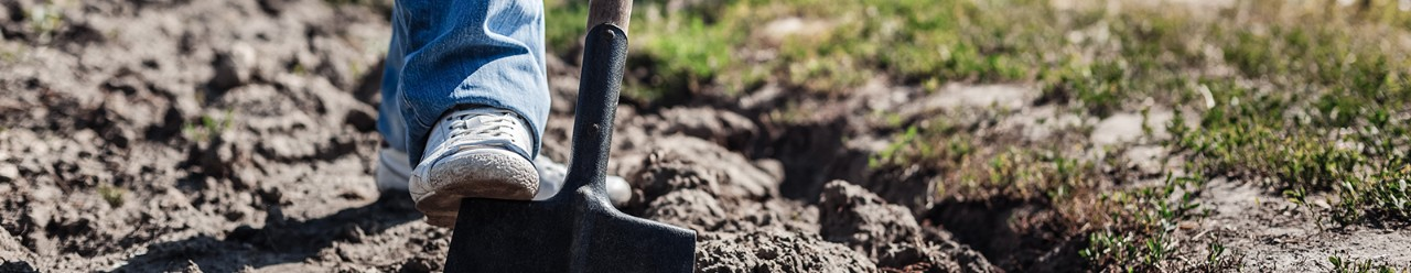 man digging in dirt with shovel
