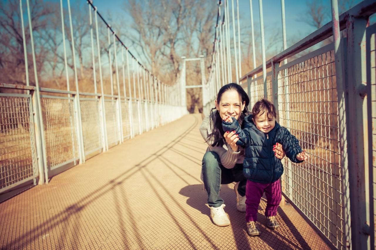 Young mother playing with baby daughter on footbridge
